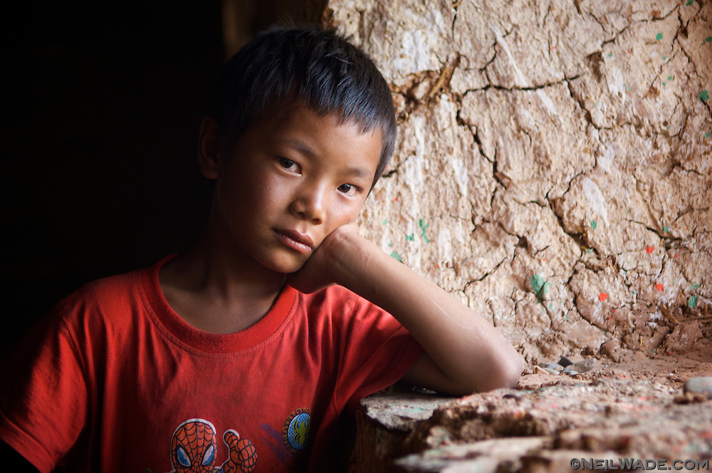 A Tibetan boy poses in a window in Dawu, Tibet.