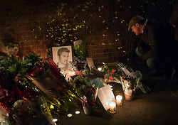 © Licensed to London News Pictures. 26/12/2016. Goring-, UK. Fans (R) look at tributes to George Michael placed at the front door of his house in Goring. Pop superstar George Michael died on Christmas day at his Oxfordshire home on the River Thames aged 53. Photo credit: Peter Macdiarmid/LNP