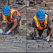 Blue collar worker repairing and replace cobblestones on city street after underground repairs.<br />