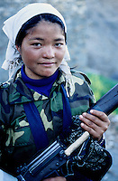 "A Maoist woman holding is gun. ""No one is forced to join the Red Army, it is their free will to become a soldier. Wegive them a six months training"" a Maoist spokesman says. ---------- Speaking to a Police officer  in Surket, he says: ""Their (Maoist Army) strong tactic is surprise. We never know when they could attack us. When someone comes towards us, we never know whether they are about to say Namaste or throw a hand grenade at us."