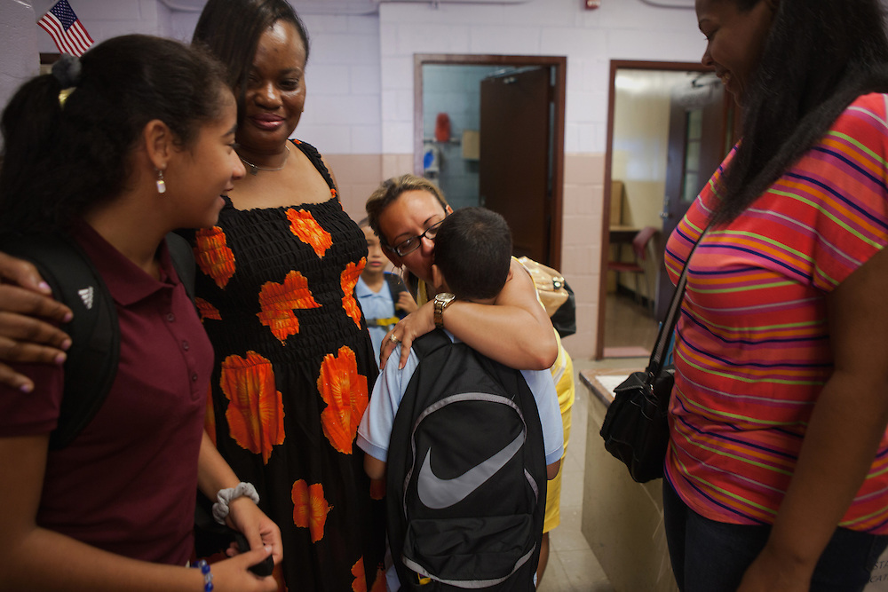 Jesus Haghighi, 7, center, is greeted by Family Engagement Coach Jeannette Diaz, center, alongside his mother Yokayra Fernandez-Haghighi , right, and his sister, Victoria Haghighi, 12, left, standing beside their former kindergarten teacher Fay Moody, at PS85 in Fordham Heights in The Bronx, NY on September 11, 2013.