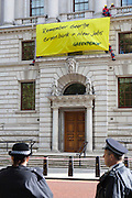 Greenpeace demonstrate above the main door of the Tresuary, Westminster, London.