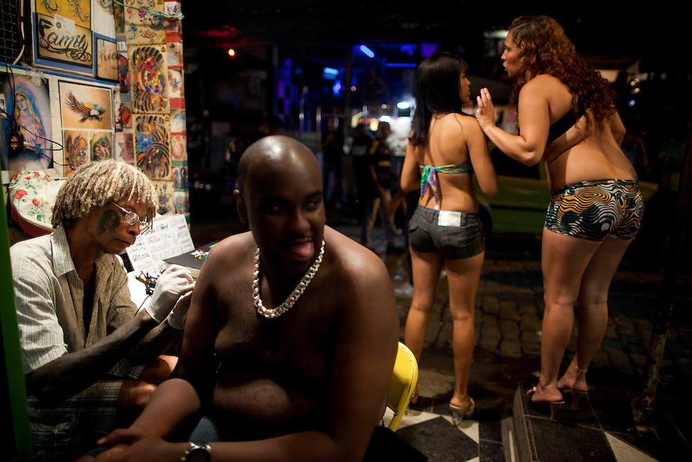 Break, left, tattoos a man, center, as sex workers wait for customers at Vila Mimosa prostitution zone in Rio de Janeiro, Brazil, Thursday, May 8, 2011. <br /> <br /> Spelling the possible end of Vila Mimosa is a high-speed train the government wants to build to link Rio to Sao Paulo, as part of Brazil's Olympic proposal. The government is expected to open bidding to prospective builders July 29.
