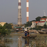 A fisherman and young boy search for snails outside the coal-powered electricty plant in Phai Lai, about 70 kilometers east of Hanoi, Vietnam, 14 September, 2007.