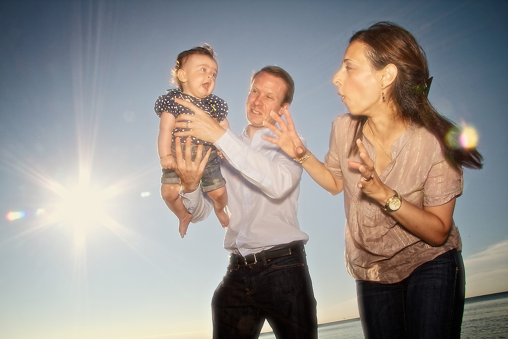 A husband and wife play with their baby girl against a sunny blue sky.