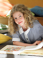 Elementary schoolgirl reading book lying on floor portrait