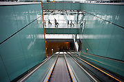 Long escalator and arriving passengers and airport architecture at Heathrow's Terminal 5.