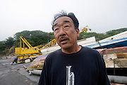 Toshikazu Takahashi, 54, looks out to sea as he stands next to damaged fishing vessels that have been pulledf from the harbor  at Kyubun on the Oshika Peninsula, Miyagi Prefecture, Japan on 31 May, 2011..Photographer: Robert Gilhooly