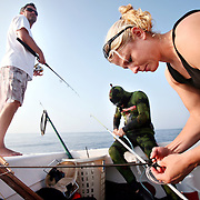 "Captain Lindsey Shuford watches as Kenneth Kelly and Kelsey Albert prepare their spearfishing gear, including guns, spears, tips and lines before freediving off the coast of North Carolina. ""Blood in the Water - Gear check"""