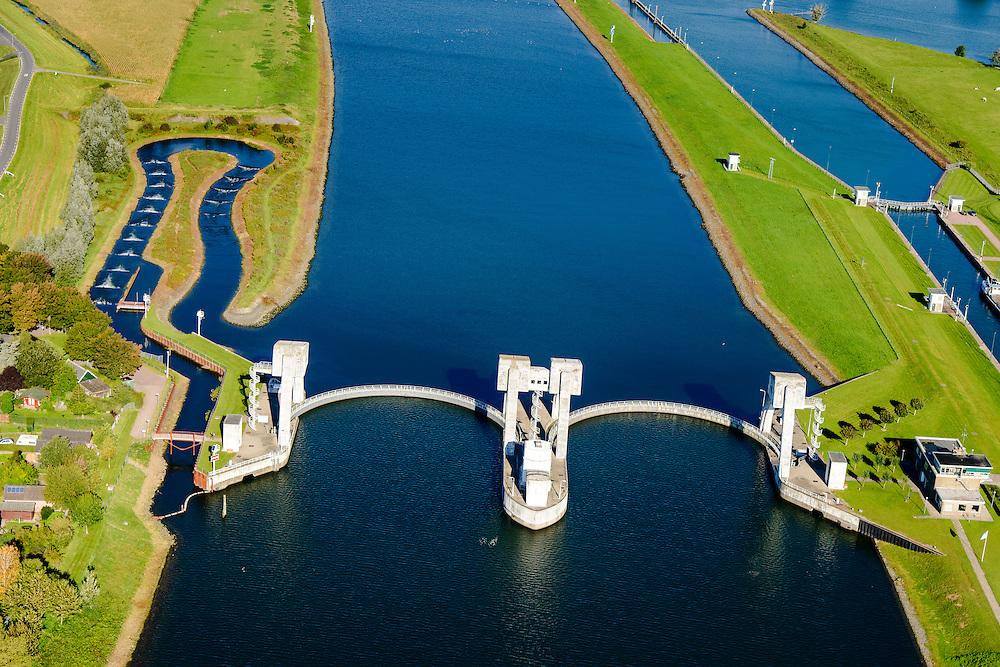 Nederland, Zuid-Holland, Hagestein, 30-09-2015; stuw in de rivier de Lek, dient om het waterpeil in de rivier te reguleren en het scheepvaartverkeer mogelijk te maken. Als gevolg van de geringe wateraanvoer is de vizierschuif gesloten, vissen kunnen gebruik maken van de de vistrap (of vispassage). Maast de stuw de schutsluis voor de scheepvaart. <br /> Weir in the river Lek, regulates and manages the water level. The Lek is a rain river, with especially in the winter large amounts of water (melt water), in the summer there is a shortage of water, the weir ensures sufficiently high water level for shipping. Next to the dam fish ladder and shipping lock.<br /> luchtfoto (toeslag op standard tarieven);<br /> aerial photo (additional fee required);<br /> copyright foto/photo Siebe Swart