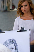 Italy, Rome, Piazza Navona Street Artist sketches a portrait of a tourist