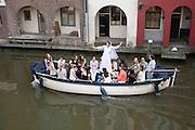 Een meisje vaart met haar vriendinnen op haar vrijgezellenfeest in een boot door de Oudegracht in Utrecht.<br /> <br /> A girl is boating with her friend at her bachelor party at the canals in Utrecht.