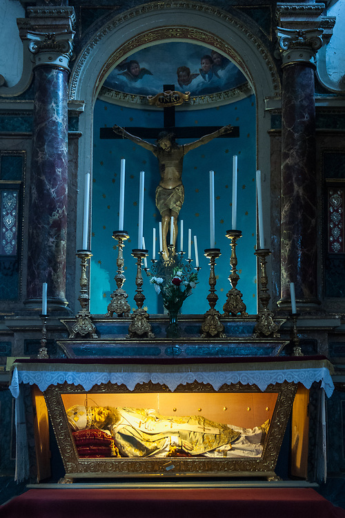 A view of the altar and of the statue of S. Ildebrando of San Donato church in the village of Civita di Bagnoregio.<br /> Civita di Bagnoregio is a town in the Province of Viterbo in central Italy, a suburb of the comune of Bagnoregio, 1 kilometre (0.6 mi) east from it. It is about 120 kilometres (75 mi) north of Rome. Civita was founded by Etruscans more than 2,500 years ago. Bagnoregio continues as a small but prosperous town, while Civita became known in Italian as La citt&agrave; che muore (&quot;The Dying Town&quot;). Civita has only recently been experiencing a tourist revival. The population today varies from about 7 people in winter to more than 100 in summer.The town was placed on the World Monuments Fund's 2006 Watch List of the 100 Most Endangered Sites, because of threats it faces from erosion and unregulated tourism.