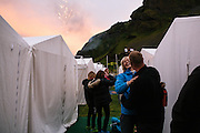 Festival goers greet each other as fireworks kick off the festivities in Vestmannaeyjar (the Westman Islands), Iceland — a small, volcanic archipelago off the southern coast of Iceland. The island is host to the annual Þjóðhátíð (Thjodhatid), a four-day, outdoor concert and cultural festival which has been celebrated since 1874, has become one of Iceland's largest and most popular festivals, attracting thousands of people to the tiny island known for its fishing industry and its puffin nesting population. Some 830,000 nesting pairs of puffins come to the Westman Islands each year to breed on the steep, grassy cliffs. But those numbers are down from over a million, as the Westman Islands are on their 11th consecutive year of complete reproductive failure and biologists are currently investigating whether warming ocean surface temperatures are driving the puffins' food supply to colder waters in the north and rendering the seabirds unable to breed in their historic nesting grounds. This population collapse has led to a number of behavior adjustments, including the reduction of consuming smoked puffin, a traditional Icelandic dish, and abbreviating the puffin hunting season in the Westman Islands to only three days this year.
