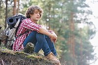 Full length of thoughtful male backpacker relaxing on cliff in forest