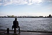 Hamburg | 30 Apr 2015<br /> <br /> A man watches the river Elbe at Landungsbruecken.<br /> <br /> &copy;peter-juelich.com<br /> <br /> [No Model Release | No Property Release]