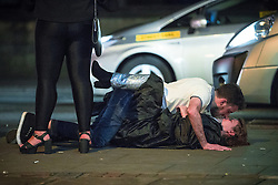 © Licensed to London News Pictures . 30/10/2016 . Manchester , UK . A couple lie on the pavement on Princess Street and kiss . Revellers on a night out , many in fancy dress , on the weekend before Halloween . Photo credit : Joel Goodman/LNP