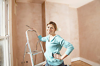 Woman standing by step ladder with scraping tool in hand