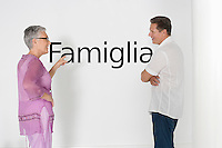 Couple discussing family issues against white wall with Italian text