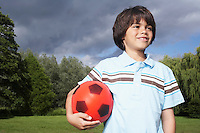 Portrait of boy (7-9) in meadow with football looking away