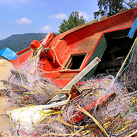 Destroyed Fishing Boat and Tangled Nets After Tsunami on Patong Beach in Phuket, Thailand<br />