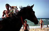 A man plays with his horse on the beach in Gaza City. (Photo/Scott Dalton)