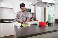 Young man cutting broccoli at kitchen counter