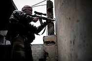 SYRIA - Al Qsair. A member of  Free Syrian Army shots toward Syrian Army position in Al Qsair, on January 24, 2012. Al Qsair is a small town of 40000 inhabitants, located 25Km south-west of Homs. The town is besieged since the beginning of November and so far it counts 65 dead. ALESSIO ROMENZI