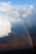 The sun shines into a heavy rain storm, forming rainbows over the crater in Haleakala National Park, Maui, Hawaii.