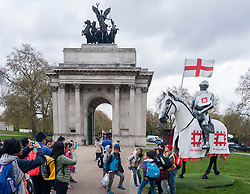 © Licensed to London News Pictures. 22/04/2015. Wellington Arch, London. Tourists take a group photo as English Heritage unveil a 15ft St George at Wellington Arch in honour of the Patron Saint ahead of England's largest St George's Day celebration at Wrest Park as well as the launch of a nationwide tour which will see the knight open jousting tournaments at castles across England. Photo credit : Stephen Chung/LNP