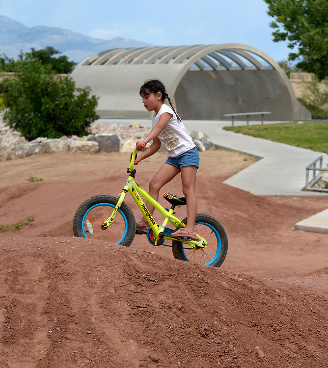 gbs053017c/ASEC -- Lashell Pedroncelli, 6, rides on the new dirt bike track at the Alamosa Skate Park on Tuesday, May 30, 2017. The full pipe skate board structure is behind her. The Park is the largest skate park in the southwest and is designed for BMX bikes, skateboards and in-line skates. (Greg Sorber/Albuquerque Journal)