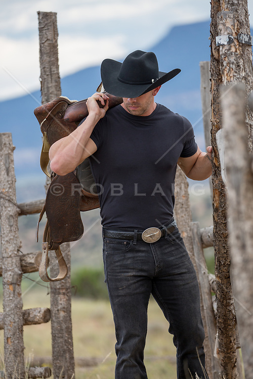 rugged muscular cowboy with a saddle on a ranch