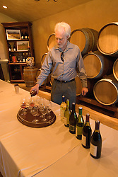 California, San Luis Obispo County: Winemaker Harry Hansen at Edna Valley Vineyards, noted for his Chardonnay.  Hansen pours wine in tasting room. Model released..Photo  caluis113-71006..Photo copyright Lee Foster, www.fostertravel.com, 510-549-2202, lee@fostertravel.com