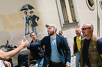 """NAPLES, ITALY - 30 JULY 2018: Roberto Saviano (center), an Italian journalist, writer and essayist is seen here with his police escort as he arrives and greets the young actors of the collective """"Nuovo Teatro Sanità"""" (New Sanità Theatre) in the Sanità neighborhood in Naples, Italy, on July 30th 2018.<br /> <br /> In 2017 the 17-year-old innocent victim Genny Cesarano was shot and killed by stray bullet  in cross fire between 2 rival gangs vying for territorial control in the Sanità neighborhood.<br /> The  isolation of the neighborhood Sanità over the years provided an ideal location for the Camorra to expand their illicit activities and profit from soaring unemployment rates and economic instability,<br /> <br /> After the first death threats of 2006 by the Casalese clan , a cartel of the Camorra, which he denounced in his exposé and in the piazza of Casal di Principe during a demonstration in defense of legality, Roberto Saviano was put under a strict security protocol. Since 2006 Roberto Saviano has lived under police protection.<br /> <br /> Saviano's latest novel """"The Piranhas"""", which tells the story of the rise of  a paranza (or Children's gang) and it leader Nicolas, will be released in the United States on September 4th 2018."""