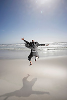 Business man jumping mid air on beach back view