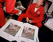 Flight Lieutenant Antony Parkinson a pilot with the elite 'Red Arrows', Britain's prestigious Royal Air Force aerobatic team, signs posters on arriving at the team's home base at RAF Scampton, Lincolnshire from his last ever display. Flt Lt Parkinson has served on the Red Arrows for four years and is to leave for a Typhoon squadron - from a relatively simple aircraft to one of the most sophisticated. Press and PR is one of the team's main purposes, acting as ambassadors for the UK and as recruiting tool for tomorrow's RAF officers and autographing publicity material is a routine chore. Traditionally, photographs are designed to allow pilots a space to sign their names alongside their respective position in the display formation. In high-spirits after a stressfully long year, he is in the crew room to wind down, with a tomato in his mouth. .  . .