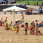 NLD/Huizen/20060705 - Mensen zoeken verkoeling aan het strand aan de Zomerkade in Huizen op de vlucht voor de warmte