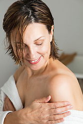 Woman Applying Body Lotion on Shoulder