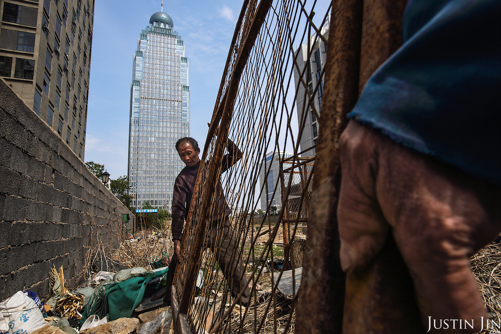Former farmers build a new high-rise -- on a plot that was farmland just a few years ago -- in Linyi city in the northeastern China. <br /> <br /> The local government is razing down this village on the outskirts of the city and turning farmland into an urban development zone. <br /> <br /> China is pushing ahead with a dramatic, history-making plan to move 100 million rural residents into towns and cities between 2014 and 2020 &mdash; but without a clear idea of how to pay for the gargantuan undertaking or whether the farmers involved want to move.<br />