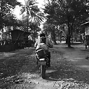 "Motorbike guide Digby Greenhalgh drives through the ""bomb village"" of Ban Senphen. The village is located in the Ban Phanhop valley, one of the ""chokes"", or narrow corridors along the Ho Chi Minh Trail in Laos that were heavily bombed by American forces during the Vietnam War. Much of the village infrastructure, from housing supports to planters, are constructed from the metal from downed airplanes and unexploded bombs. .."