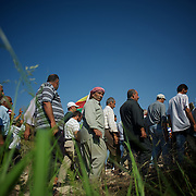 August 12, 2012 - Kafa Safra, Efrin, Syria: Syrian Kurdish men arrive at the funeral and ceremony of martyrdom of Taliz Gadalum, a Kurdistan Workers' Party (PKK) fighter killed days earlier during combat against the Turkish army...PKK has been fighting an armed struggle against the Turkish state for an autonomous Kurdistan and greater cultural and political rights for the Kurds in Turkey, Iraq, Syria and Iran. Founded on 27 November 1978 in the village of Fis, was led by Abdullah Öcalan. The PKK's ideology was originally a fusion of revolutionary socialism and Kurdish nationalism - although since his imprisonment, Öcalan has abandoned orthodox Marxism. The PKK is listed as a terrorist organization by Turkey, the United States, the European Union and NATO. (Paulo Nunes dos Santos)