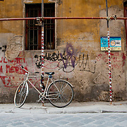 A single 10-speed bicycle leans up against some metal scaffolding along Borgo Santa Croce, a cobble stone street in downtown Florence, Italy. There is graffiti on the wall and bars on the window.