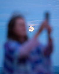© Licensed to London News Pictures.20/06/2016. Glastonbury, Somerset, UK. A woman takes pictures on a mobile phone in front of a 'Strawberry full moon' at sunset on Glastonbury Tor as people prepare to celebrate the Summer Solstice and the shortest night of the year on top of Glastonbury Tor. This year is a leap year and so the actual Solstice fell on 20 June. There was also a 'Strawberry' full moon to coincide with the Solstice, the first time for decades. Photo credit : Simon Chapman/LNP