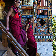 Two buddhist monks going down the stairs of Punakha Dzong, Punakha, Bhutan, Asia