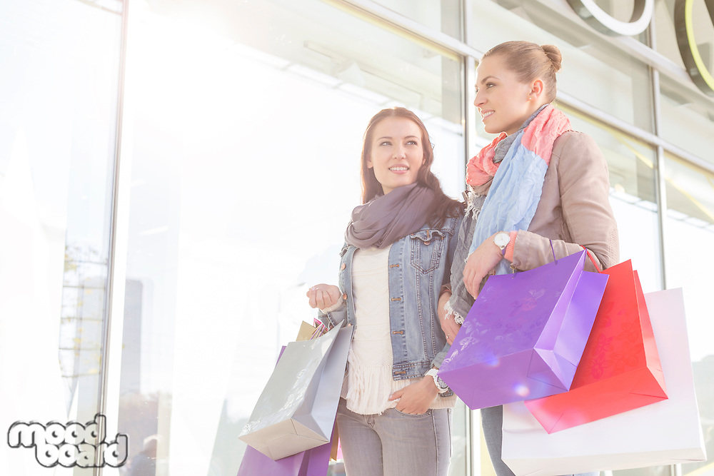 Young women carrying shopping bags by store
