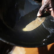 Part of the gold extracting process is to sieve the bigger pieces of gold out of the mudd made from crushed stones and water. Here gold dust is shining in the sun. The mines in the small community near Bolgatange in Northern Ghana are dug with shovels and spades and held up by timber, all very precarious. The mine shafts go deep into the ground and run along under the surrounding fields. The small community which has sprung up around the gold finds consists of poor people from all over Northern Ghana,most of them now stuck, not making much money and in dept to their gold dealers.