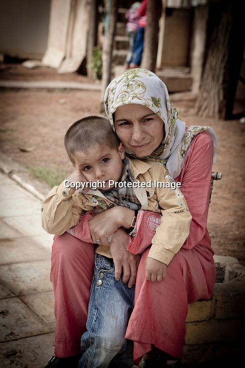 Desolate mother and son Syrian Kurdish refugees seating in the court yard of  a mosque located in the boarder town of Suruc, Turkey.