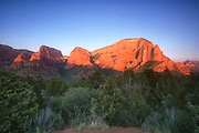 The Kolob Canyons, also called the Kolob Fingers, are turned red at sunset in Zion National Park in Utah. The towering Shuntavi Butte is visible on the right side of the image. The Kolob Canyons are also known as finger canyons, with tall, narrow formations separated by narrow canyons.