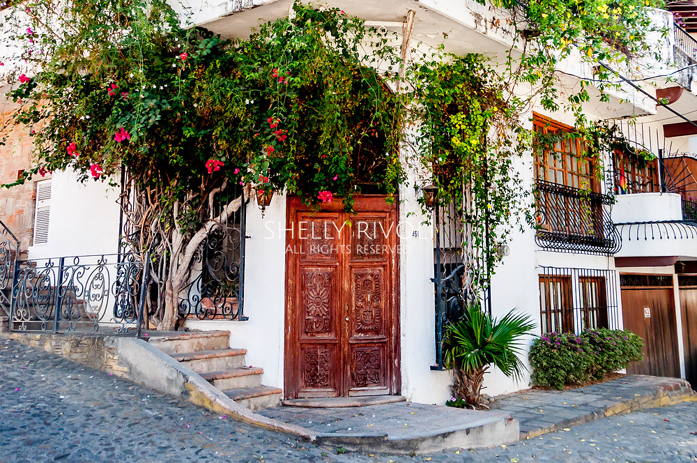 Carved wooden doors in Puerto Vallarta's Zona Romantica, with bougainvillea vines and wrought iron adding romance to to the white building on a street corner in the romantic zone.