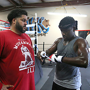 Professional boxer Erickson Lubin wraps his hands as his coach looks on at the School of Hard Knocks boxing gym in preparation for his upcoming world title fight on Monday, August 18, 2017 in Orlando, Florida.  (Alex Menendez via AP)